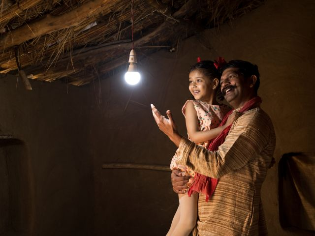 Rural,Indian,Father,With,Daughter,Delighted,On,Electricity,Reaching,Their