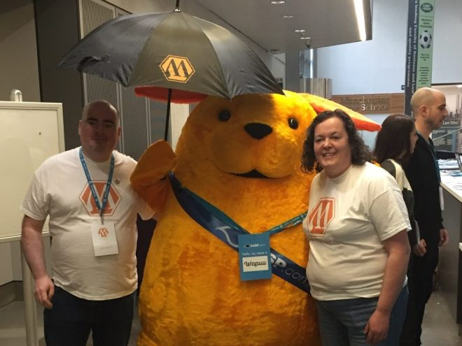 Wapuu meets WordCamp Manchester organisers and picks up a brolly for the Manchester rain