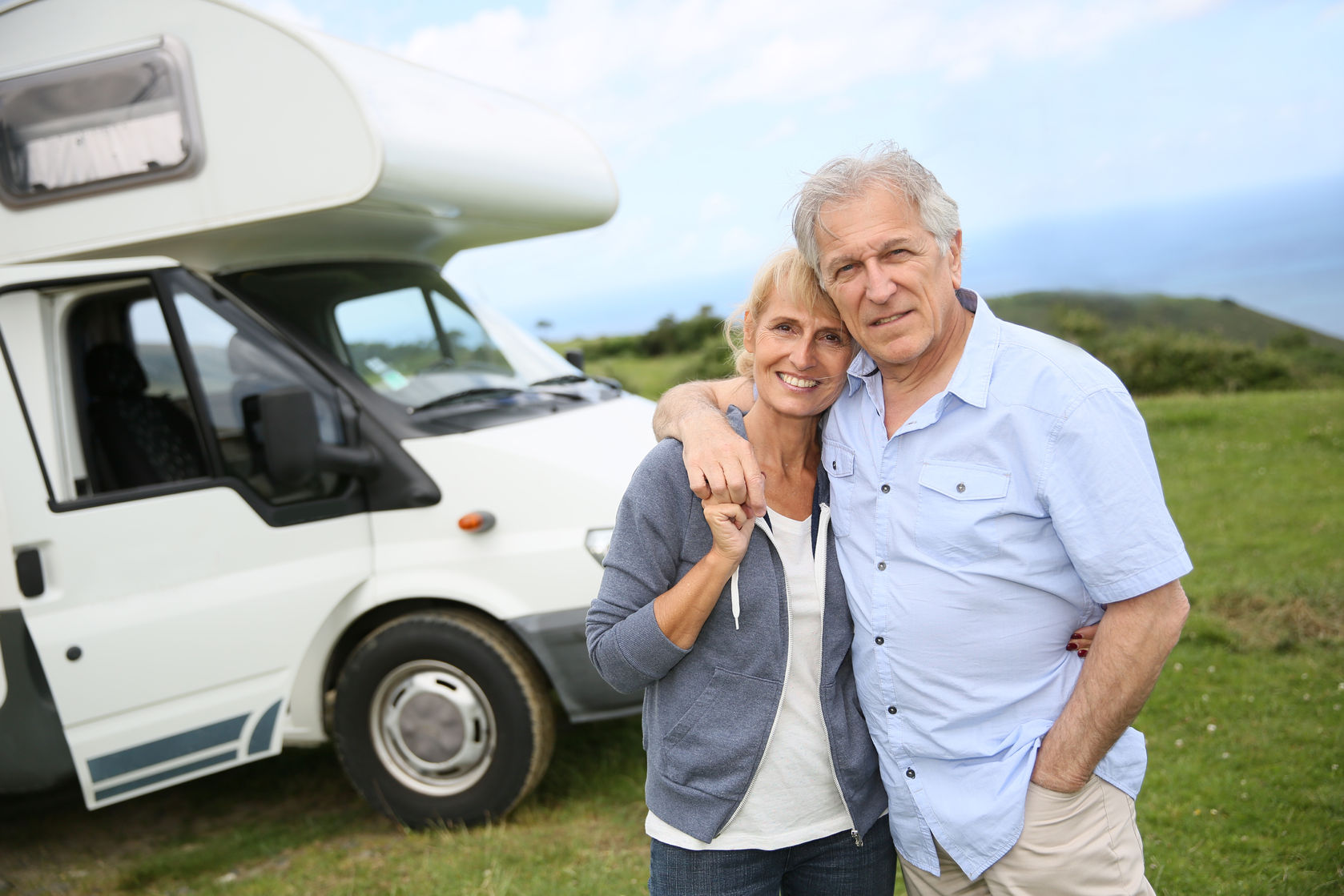 30205153 - happy senior couple standing in front of camping car