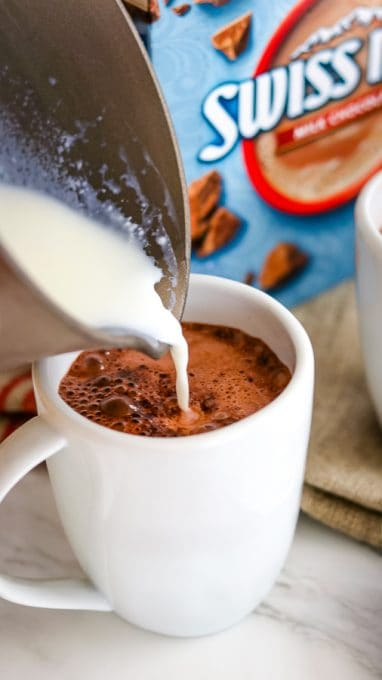 Pouring warm milk into mugs to make Chocolate Covered Cherry Hot Chocolate.
