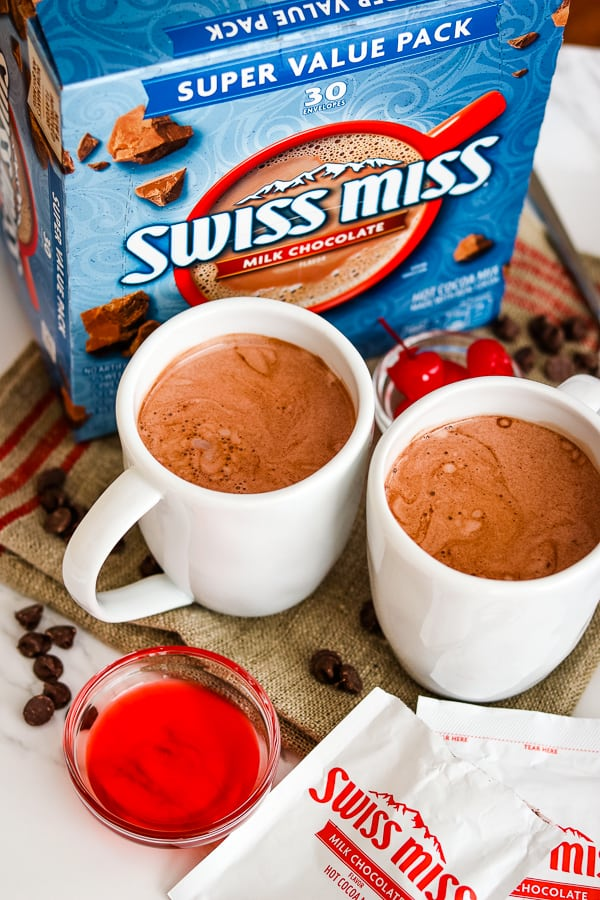 A box of Swiss Miss Hot Chocolate, two mugs of Chocolate Covered Cherry Hot Chocolate, cherry juice and chocolate chips.