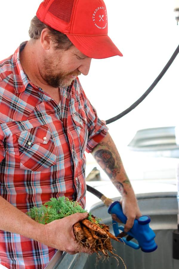 Owner Erich Schultz of Steadfast Farm, Mesa, AZ washing carrots.