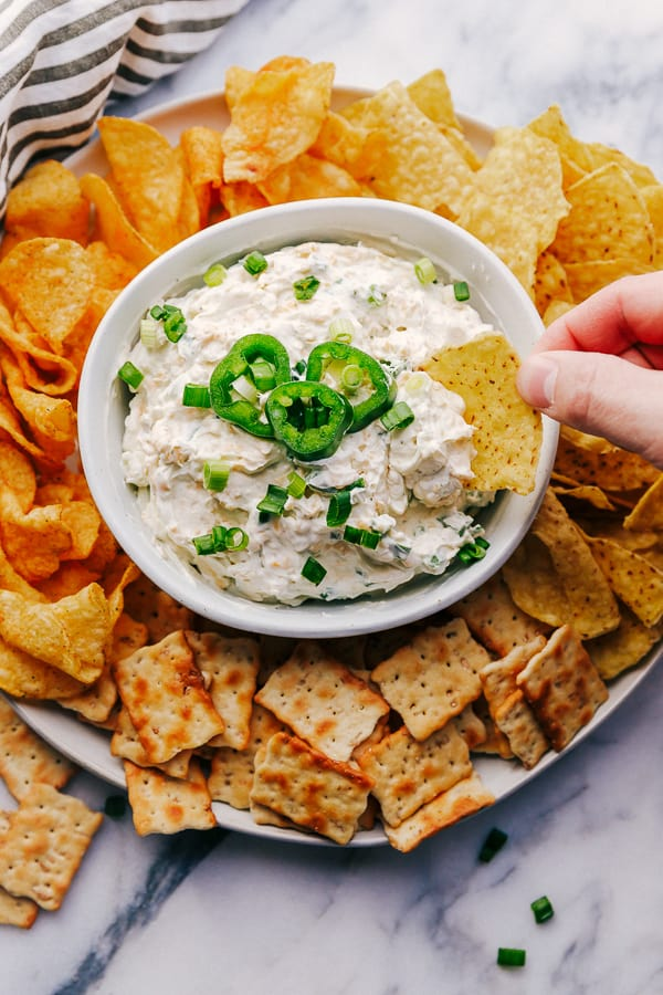 Jalapeño Ranch Dip in a bowl surrounded by chips and crackers.