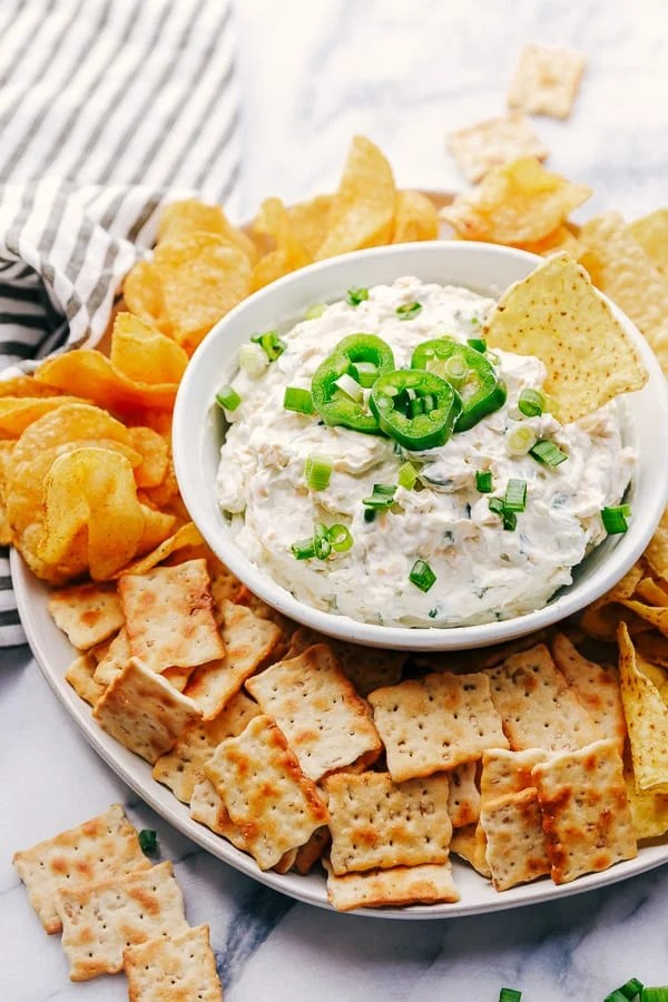 Jalapeño Ranch Dip with a chip surrounded by chips and crackers.