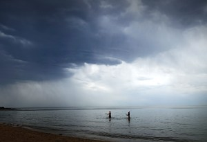Couple under clouds in the water at Brighton Beach