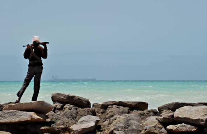 TO GO WITH AFP STORY BY JEAN-MARC MOJON A pirate stands on a rocky outcrop on the coast in Hobyo, central Somalia, on August 20, 2010 as he looks at a hijacked Korean supertanker anchored on the horizon. The Marshall Islands-flagged VLCC Samho Dream is a third of a kilometre long, one of three largest vessels ever hijacked by pirates, and carries an estimated 170 million dollars of Iraqi oil destined for the United States. Fighting a losing battle against the sand that has already completely covered the old Italian port, Hobyo's scattering of rundown houses and shacks looks anything but the nerve centre of an activity threatening global shipping. Hobyo pirates have collected millions of dollars in ransoms over the past two years. They even have currency checking and counting machines for the bags of air-dropped cash they receive. AFP PHOTO / ROBERTO SCHMIDT (Photo credit should read ROBERTO SCHMIDT/AFP/Getty Images)