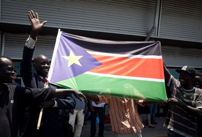 ISRAEL OUT South Sudanese migrants wave their national flag as they wait to board a bus to Ben Gurion Airport, near Tel Aviv, where they will be deported to south Sudan on June 17, 2012. Some 120 people from Southern Sudan will take the first flight back home as part of a nationwide crackdown to expel thousands of illegal African migrants from Israel. AFP PHOTO / OREN ZIV / ACTIVE STILLS        (Photo credit should read OREN ZIV/AFP/GettyImages)