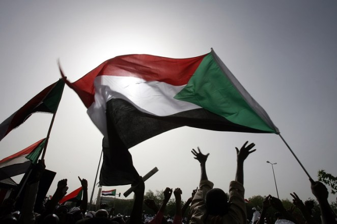 Sudanese wave national flags as they gather outside the Defence Ministry in the capital Khartoum on April 20, 2012 to celebrate retaking the oil town of Heglig from South Sudanese forces. Border clashes between Sudan and South Sudan escalated last week with waves of air strikes hitting the South, and Juba seizing the north's Heglig oil hub on April 10. AFP PHOTO/ASHRAF SHAZLY (Photo credit should read ASHRAF SHAZLY/AFP/Getty Images)