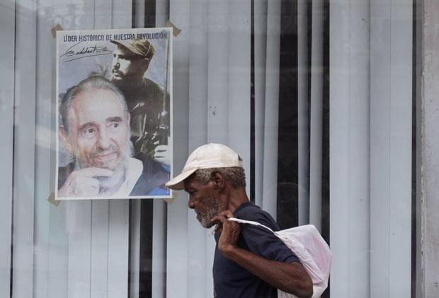 Cubano passa por cartaz com a imagem de Fidel Castro nesta segunda-feira (12) em Havana (Foto: AFP)