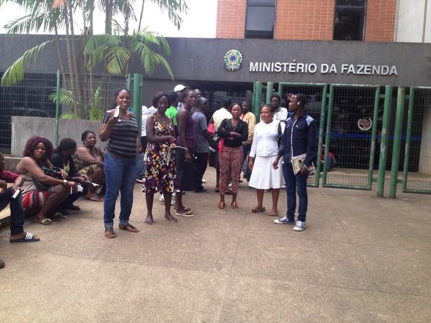 Imigrantes fazem fila em frente ao Ministério da Fazenda nesta quarta-feira (4); cheia provoca demora na retirada de documentos (Foto: Aline Nascimento