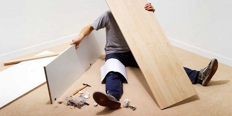 A man struggles to assemble flat-packed furniture