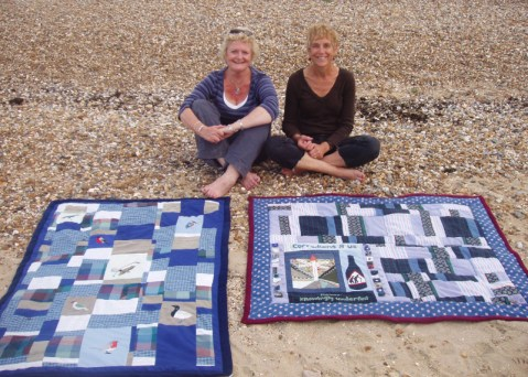 Mary & Sheila display their walking group quilts on the beach