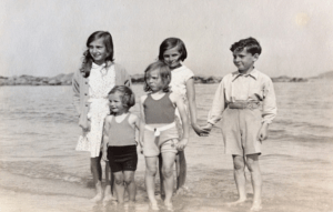 Auntie Sheila (back left), Auntie Irené (front centre), my father and the chauffeur's children on the beach