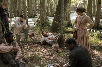 BTS: Gary Ross rehearses a scene in the Knight Company camp set with Gugu Mbatha-Raw, Donald Watkins, and others