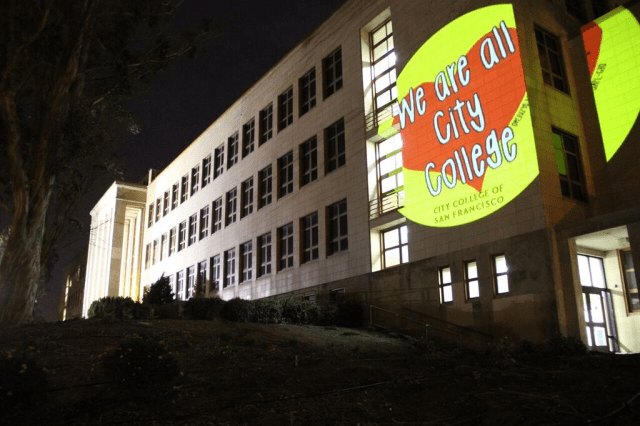 A projector puts an image on the side of the main City College building