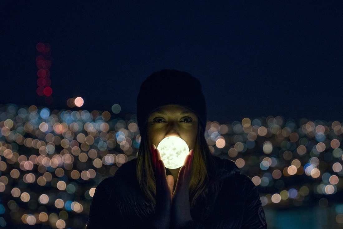 """""""Lizzy holds her handmade moon light up on Bernal with Twin Peaks in the background."""" Photo: Jake Landon, @jakelandon. #SFGuide Featured Photographer."""
