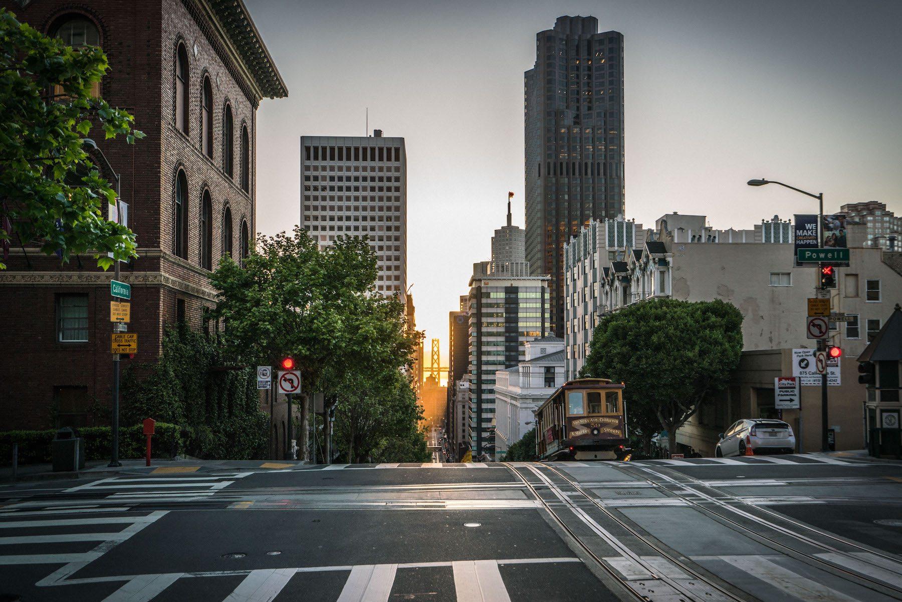 """Sun shines through the buildings downtown as a trolley descends down California."" Photo: Jake Landon, @jakelandon. #SFGuide Featured Photographer."