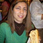 Estou segurando o sanduiche de lula com um sorriso meio torto, cara de quem não está lá muito feliz em ter que comer o negóci...risos