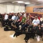Foto tirada do palco para platéia, mostra os usuários de cães guia com seus cães deitados a frente, estamos na primeira fileira, e alguns participantes ao fundo