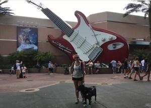 Mellina está em pé com Hilary a direita da foto, estão ao centro e ao fundo uma guitarra gigante e o letreiro Aerosmith Roller Coaster