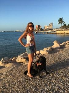 Mellina está em pé em um chão de predinhas, Hilary a seu lado sentada e ao fundo o mar e algumas palmeiras