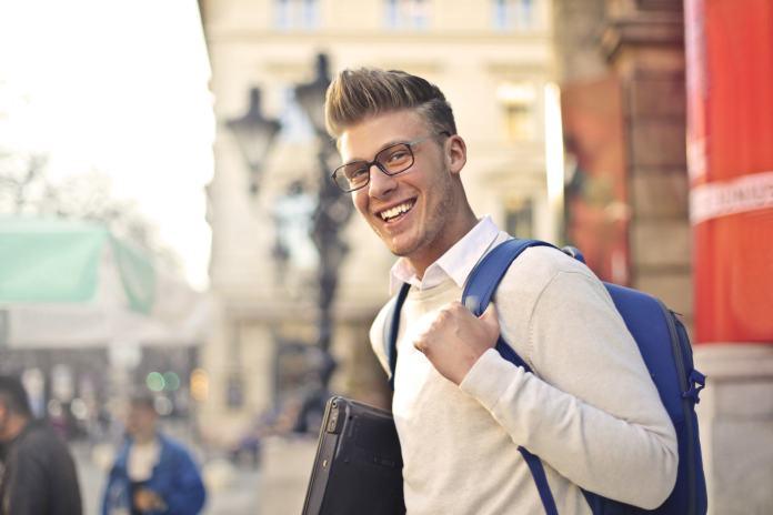 Lächelnder junger Mann mit Rucksack