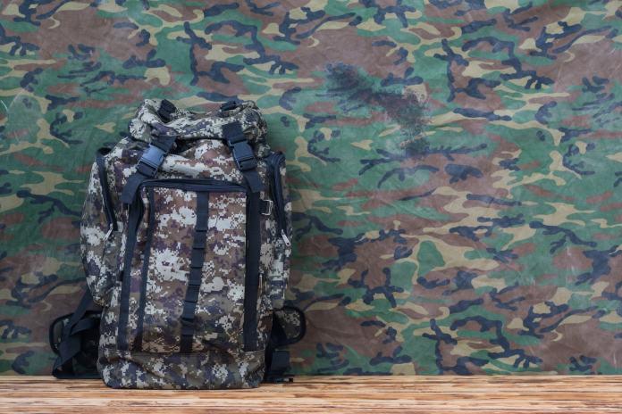 Militärischer Rucksack an Camouflage-Wand
