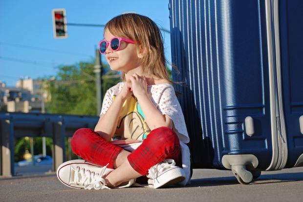 Kleines Mädchen mit großem Koffer