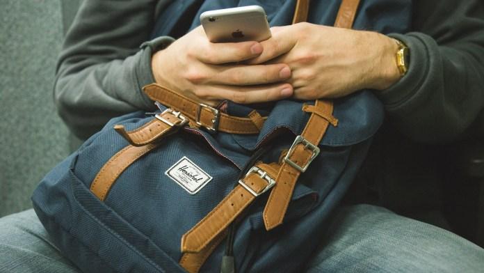 Junger Herr mit Smartphone und elegantem Rucksack