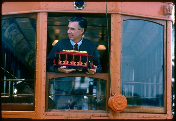 35mm color positive slide; folder 01, slide sleeve 01, slide 37; Mister Rogers' neighborhood: trolley museum shoot. Fred Rogers leans out of the window of a trolley car, holding the Neighborhood Trolley from Mister Rogers' Neighborhood.