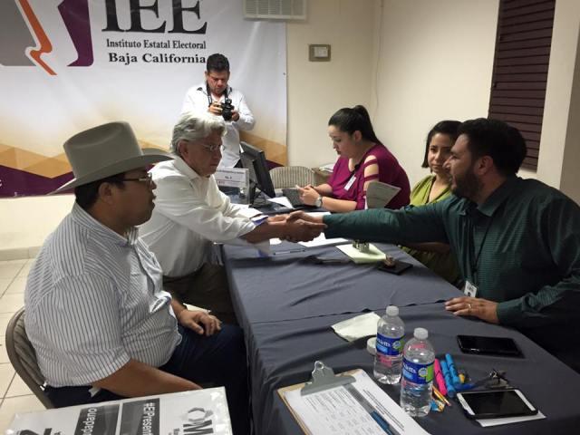 Mario Zepeda (a la izquierda, estrechando la mano de un funcionario electoral), asoirante a candidato independiente a munícipes (Fpto: Cortesía IEEBC).