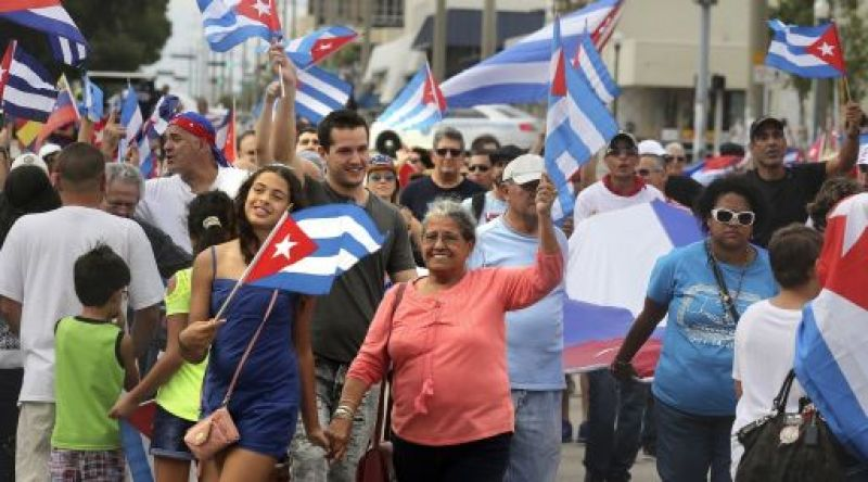 People wave Cuban flags as they walk along Calle Ocho in Miami's Little Havana Saturday, Nov. 26, 2016, following the announcement of former Cuban leader Fidel Castro's death. (Marsha Halper/Miami Herald via AP)