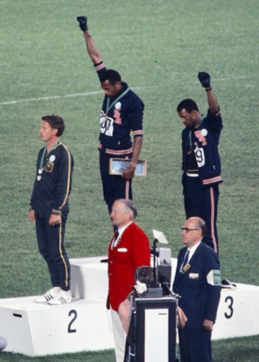 The american sprinters Tommie Smith,John Carlos and Peter Norman during the award ceremony of the 200 m race at the Mexican Olympic games. During the awards ceremony, Smith and Carlos protested against racial discrimination: they went barefoot on the podium and listened to their anthem bowing their heads and raising a fist with a black glove. Mexico City, Mexico, 1968 Mexico city, Mexico, 1968