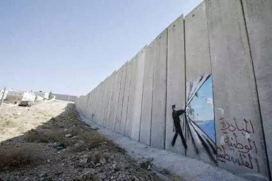 Com spray, faz críticas políticas. Aqui, o muro que divide Israel da Palestina