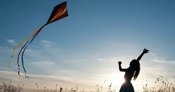BN8GKC Young Girl having fun flying a multicoloured kite in the English countryside. Silhouette