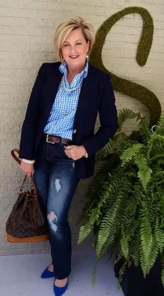 Calça jeans rasgada, com blazer escuro por cima da camisa clara
