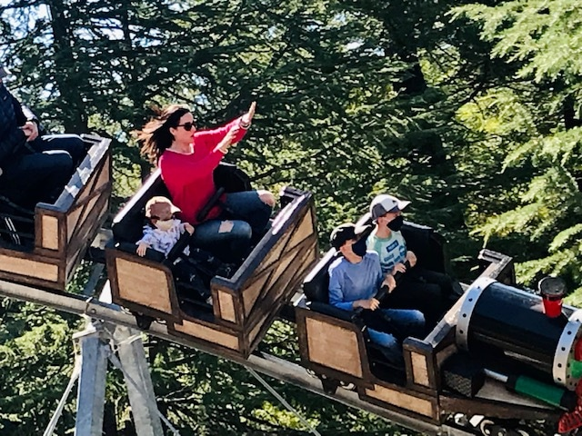 mom and kids riding roller coaster