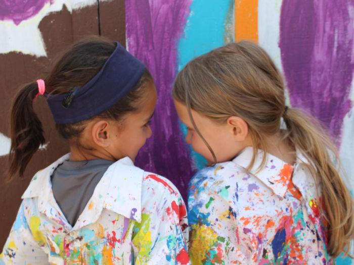 black pine circle kids in front of mural