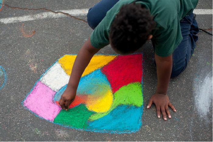 student drawing with sidewalk chalk