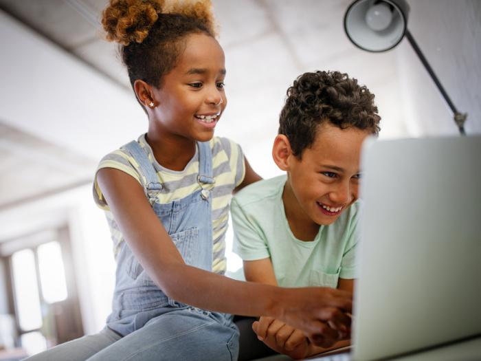 siblings on laptop laughing