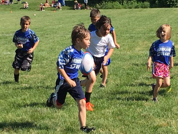 Six children running on a green grass field. Four children are wearing blue rugby uniform shorts. Two Children wearing white t-shirts. The child in the foreground is carrying the ball in one hand. His head is held high as he scans the defense. The other children are chasing the ball carrier.