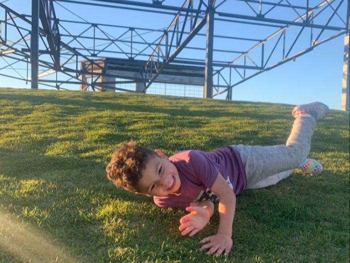 child rolling down grassy hill