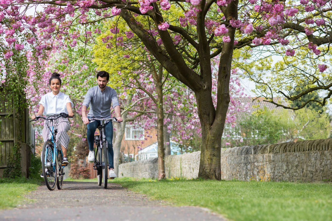 Couple riding push bikes on footpath