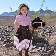 girl wearing handmade cowgirl outfit made by 5 dog farm