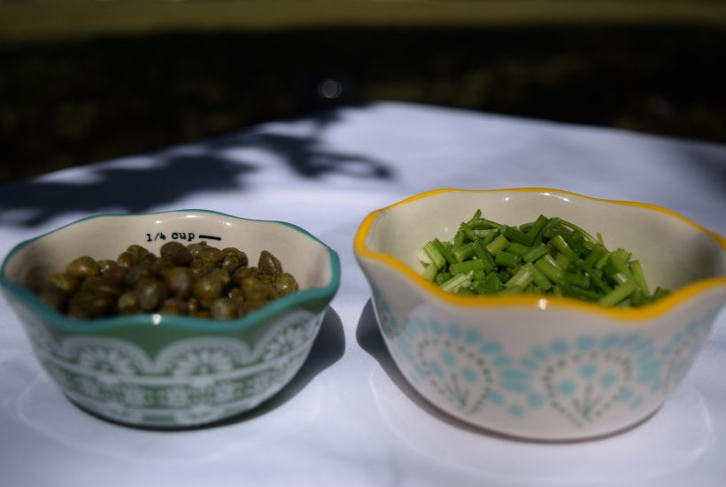 chopped parsley stems and capers in bowls