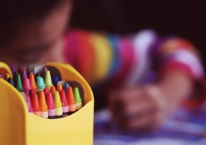 child drawing with crayons in developmentally appropriate kindergarten