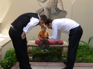 A toddler sits on a bench being fussed over by friendly Turkish hotel staff
