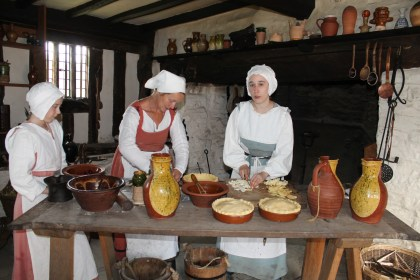 Costumed actors prepare Elizabethan-era baked goods.