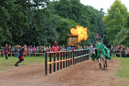 A costumed rider sets fire to a target bag with his flaming lance