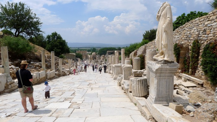 A paved ancient walk lines with statues